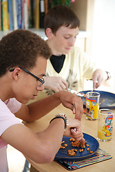 Two youths eating beans on toast.