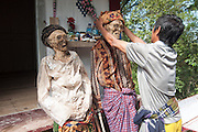 Zombie chic: Indonesian province's bizarre annual ritual of digging up its dead to give them a wash, groom and dress them in new clothes<br /> <br /> They say the dead live on in our hearts and minds - but in one Indonesian province, the deceased continue to walk the earth in a rather more literal, zombie-like fashion. <br /> Families in Toraja in South Sulawesi dig up the bodies of their dead relatives before washing, grooming and dressing them in fancy new clothes. <br /> Even dead children are exhumed - two of these photos show the skeleton of a baby wrapped in a print dress with a doll laid next to it. <br /> Damaged coffins are fixed or replaced, and the mummies are then walked around the province by following a path of straight lines. <br /> The ritual is called Ma'nene, or The Ceremony of Cleaning Corpses.<br />  According to the ancient Torajan belief system, the spirit of a dead person must return to his village of origin. <br /> So if a person died on a journey, the family would go to the place of death and accompany the deceased back home by walking them back to the village.<br /> In the past, people were frightened to journey far, in case they died while they were away and were unable to return to their village.<br /> <br /> Photo shows: Zombieland: The bodies resemble something out of a horror film as they are dug up every year to be washed and dressed up in new clothes<br /> ©Exclusivepix Media