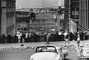 Free Show: Sidewalk superintendents looked over the wall at First Avenue and Seneca Street to observe work on the $390,000 ramp under construction from the Alaskan Way Viaduct's northbound deck. (The Seattle Times, 1961)
