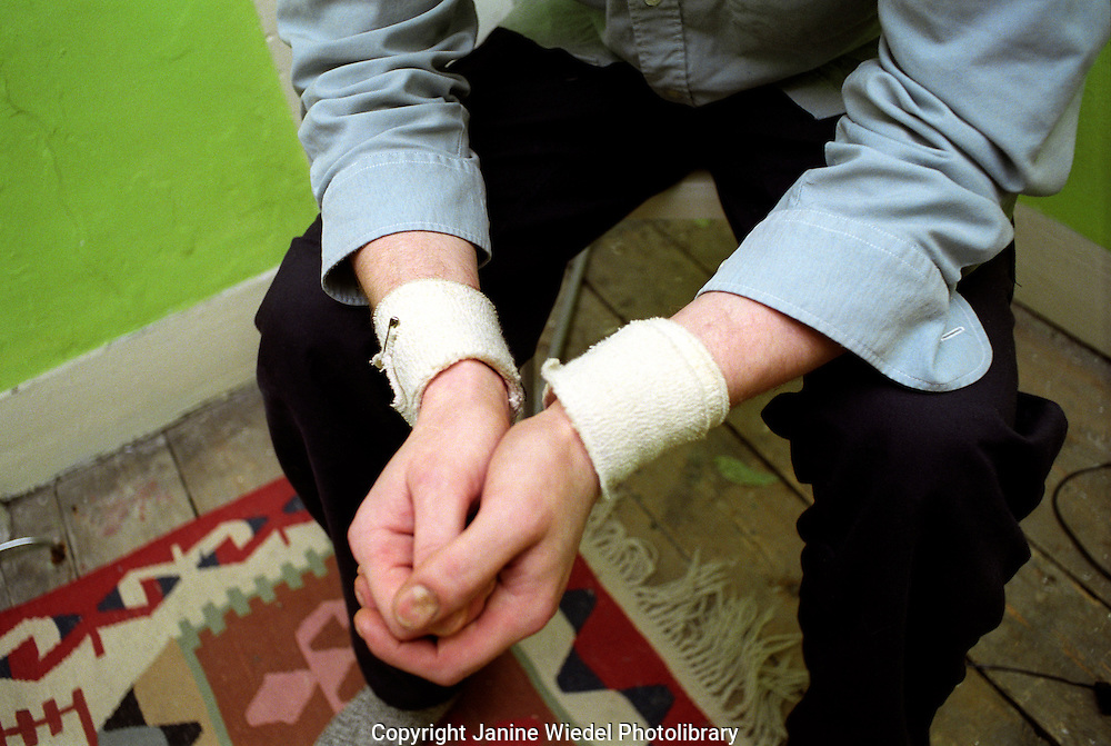 Man with deep depression and bandaged wrists from suicide attempt.