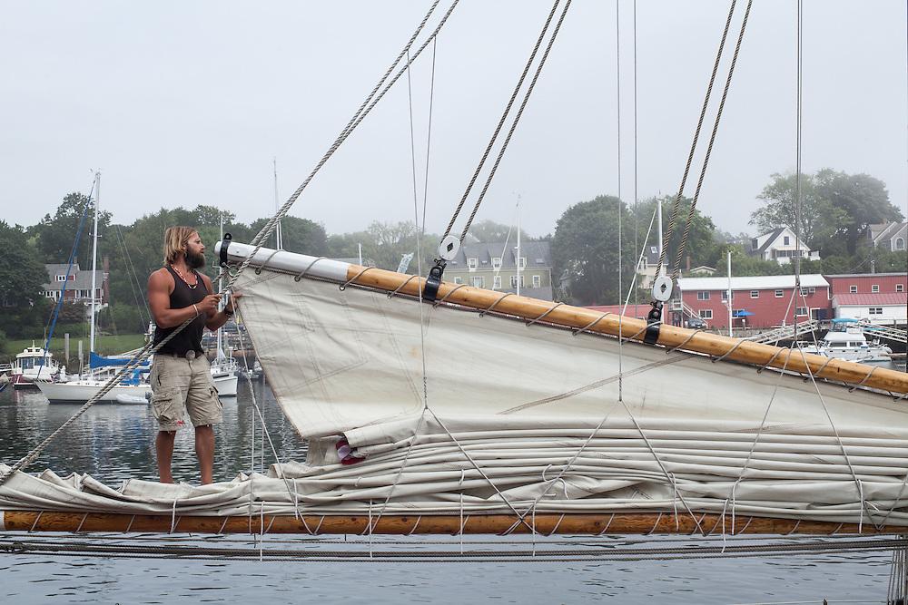 A deckhand furls the mainsail aboard the windjammer schooner Appledore II at the dock in Camden, Maine.