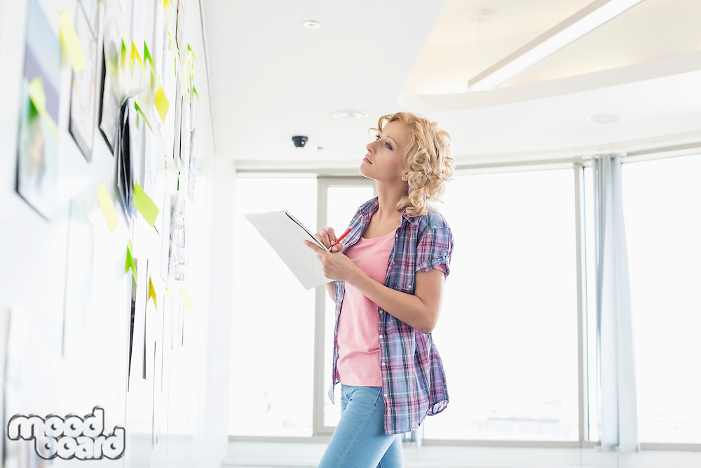 Creative businesswoman looking at papers stuck on wall while writing notes in office