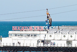© Licensed to London News Pictures. 23/06/2018. Brighton, UK. Members of the public take a ride in the Zip Wire attraction on the beach in Brighton and Hove as sunny and warmer weather is hitting the seaside resort. Photo credit: Hugo Michiels/LNP