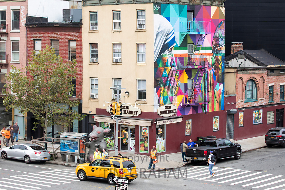 Street corner scene with yellow cab, traffic lights, mural and Chelsea Square Market store at West 18th Street and Tenth Avenue in New York City, USA
