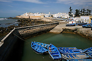 Morocco, Essaouira. Blue boats and the walls of the medina in Essaouira.