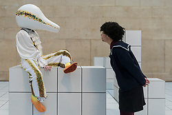 "© Licensed to London News Pictures. 21/03/2018. LONDON, UK. A woman looks at a performer wearing a squash-like costume the preview of ""The Squash"", an immersive installation combining performance and sculpture by 2016 Turner Prize nominee Anthea Hamilton.  At Tate Britain, performers will wear outfits from a collection of seven elaborate squash-like costumes to showcase Hamilton's work amidst 7,000 white floor tiles spanning the entire Duveen Galleries and Tate Britain's own sculpture collection.  The show runs 22 March to 7 October 2018.  Photo credit: Stephen Chung/LNP"