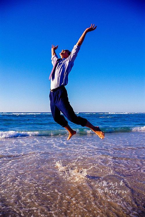 Australia --- Ecstatic Businessman Jumping in Air at the beach
