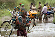 A man carries a bicycle on his shoulder across an overflowing river near the town of Amakpa, Benin on Tuesday September 18, 2007.