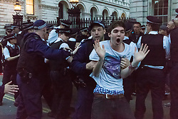 London, May 27th 2015. His jeans falling down and protesting his innocence, a protester is detained at the end of a demonstration outside Downing Street, against the Tories' ongoing campaign of austerity on the day the Queen delivered her speech to Parliament