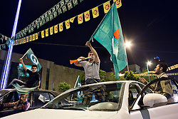 © Licensed to London News Pictures. 27/04/2014. Sulaimaniya, Iraq. A supporter of the Patriotic Union of Kurdistan (PUK) political party waves his party's flag and blows a vuvuzela during celebrations in the lead up to the 2014 Iraqi parliamentary elections in Sulaimaniya, Iraqi-Kurdistan.<br /> <br /> Although banned in other parts of Iraqi-Kurdistan, the days leading up to an election in Sulaimaniya sees political supporters of all the three main parties parading up and down the main street of the city, waving flags, honking horns, letting off fireworks and firing pistols and rifles into the air.<br /> <br /> The period leading up to the elections, the fourth held since the 2003 coalition forces invasion, has already seen six polling stations in central Iraq hit by suicide bombers causing at least 27 deaths. Photo credit: Matt Cetti-Roberts/LNP