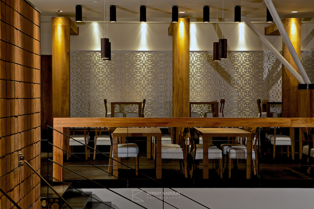 Interior design details of Georgian restaurant Shoti in Kyiv, Ukraine. First floor view with brick wall on the left, tables and supporting wooden pillars.