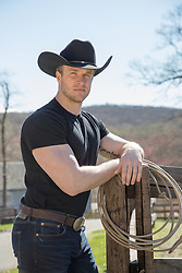 hot rugged cowboy leaning on a fence post