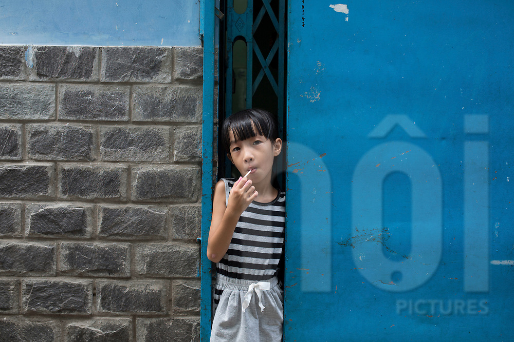 Portrait of a young Vietnamese girl with her lollipop, Ho Chi Minh City, Vietnam, Southeast Asia