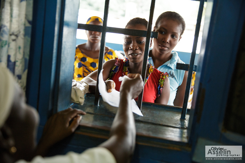 Rita Sahi, 25, who is 7-month pregnant with her third child, picks up her prescription from the pharmacy counter of the Libreville health center in Man, Cote d'Ivoire on Wednesday July 24, 2013.