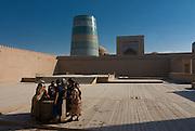 Women before a  Tower, minarett of Ichon-Qala Fortress, Khiva, Uzbekistan