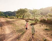 "NUBA MOUNTAINS, SUDAN – JUNE 9, 2018: Travelers pass on foot between Hieban town and Kouda, the cultural center of Hieban County.<br /> <br /> In 2011, the government of Sudan expelled all humanitarian groups from the country's Nuba Mountains. Since then, the Antonov aircraft has terrorized the Nuba people, dropping more than 4,080 bombs on hospitals, schools, marketplaces and churches. Today, vestiges of the Antonov riddle the landscapes of daily life, where more than 1 million Nuba live in famine conditions – quietly enduring the humanitarian blockade intended to drive them out of the region. The skies are mostly clear. Yet the collective memory of the bombings remains an open wound, and the Antonov itself a persistent threat. So frequent were the attacks that the Nuba nicknamed the high flying aircraft and its dismal hum: ""Gafal-nia ja,"" they would declare, running to the hillsides. ""The loss of appetite has come."""