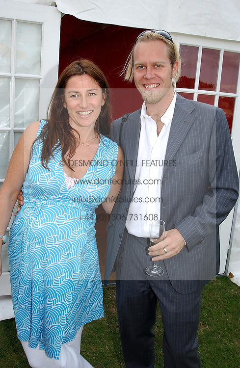 SEBASTIAN PEARSON and his fiancé AMANDA AUSTIN he is the illegitimate son of Viscount Cowdray at the Veuve Clicquot sponsored Gold Cup or the British Open Polo Championship won by The  Azzura polo team who beat The Dubai polo team 17-9 at Cowdray Park, West Sussex on 18th July 2004.
