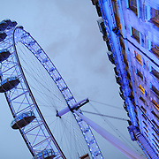 London Eye at Dusk with Buildings. The London Eye (formerly known as the Millennium Wheel) at dusk against an overcast sky.