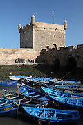 ESSAOUIRA, MOROCCO - MAY 10 : A general view of boats moored by the Skala of the Port on May 10, 2009 in Essaouira, Morocco. The traditional blue painted wooden boats lie close together in the harbour at low tide overlooked by the wall and tower of the 18th century Skala in the morning sunshine. Essaouira, on the windswept Atlantic coast of Morocco, was re-built in the 18th century by French architect Theodore Cornut to the orders of Sultan Ben Abdullah. Surrounded by ramparts it is a charming small town now becoming more popular with tourists. (Photo by Manuel Cohen)