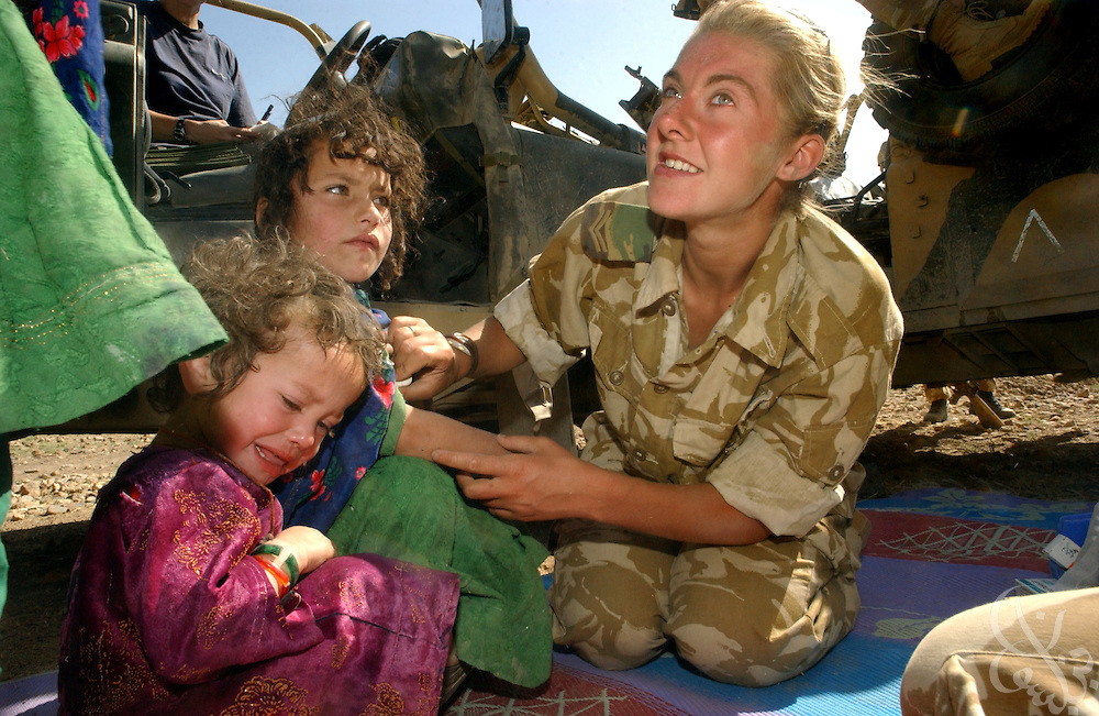 British field medic Corp. Cerianne Brown treats local Afghan children June 21, 2002 during a humanitarian aid visit to the village of Dandar in Central Afghanistan. Britain announced the day before that it will withdraw the majority of its forces beginning the first week of July.