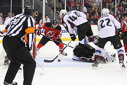Mar 15; Newark, NJ, USA; Colorado Avalanche center Mark Olver (40) sweeps the puck away from New Jersey Devils center Jacob Josefson (16) during the second period at the Prudential Center.