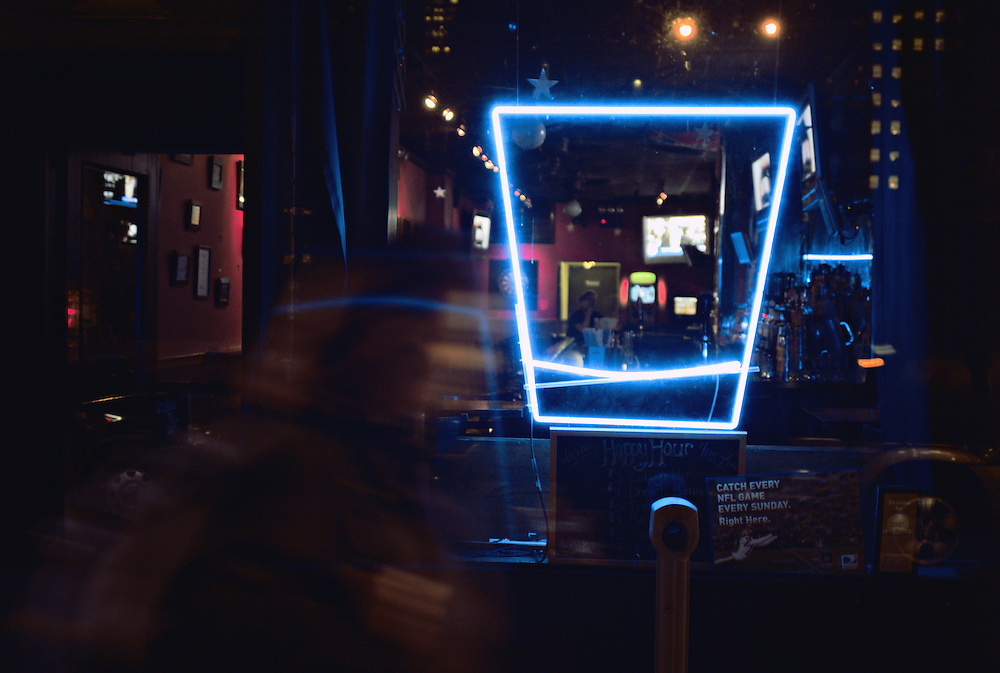 Woman, out of focus, passes blue neon sign in shape of drinking glass in bar window at night, Midtown Manhattan, New York, US