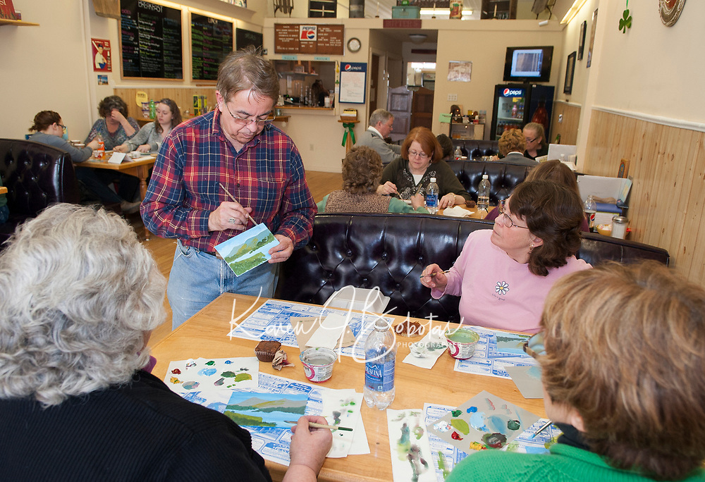 Larry Frates works with Sharyn Childs, Lois Philbrick and Jennifer Muzzey as they paint an Irish landscape at the Vintage Cafe in the downtown Laconia on Saturday afternoon.  (Karen Bobotas/for the Laconia Daily Sun)