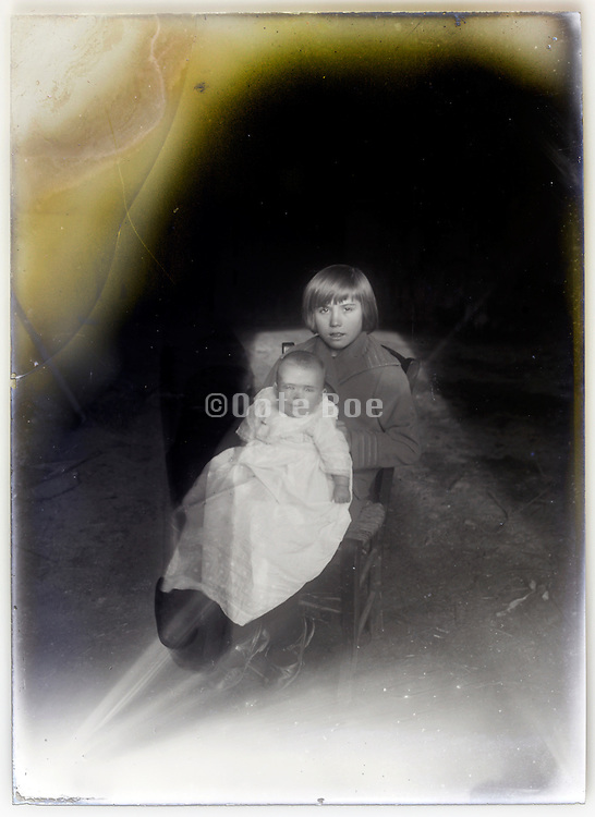 vintage fading glass plate of young girl posing with a baby