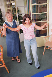 Teenage girl with physical disability walking with support of carer in residential respite care home,