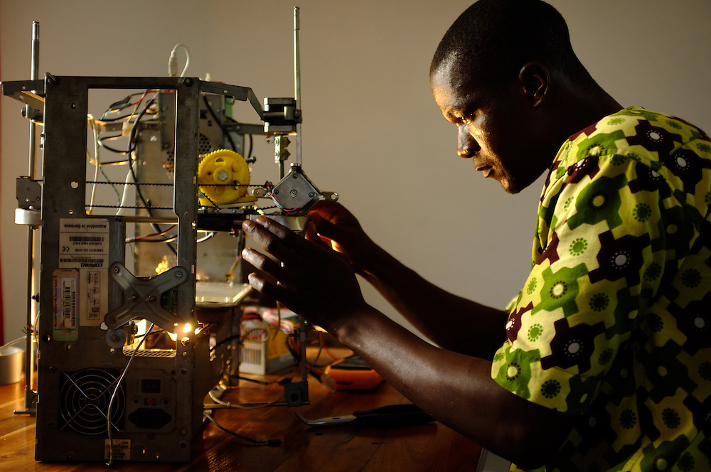 "LOME, TOGO  13-05-31   -  Kodjo Afate Gnikou and his $100 US 3D printer W.AFATE, which is largely made of e-waste, in Lome, Togo on May 31, 2013. Gnikou dreams of sending a larger version to Mars to print tools and homes for future colonizations. ""They all say it is merely a dream and it will never happen,"" says Gnikou, pointing out that there are already robots on Mars. ""I really want my 3D printer to be the first on Mars so people can say it was an African who had the idea to put a 3D printer on Mars.""  Photo by Daniel Hayduk"