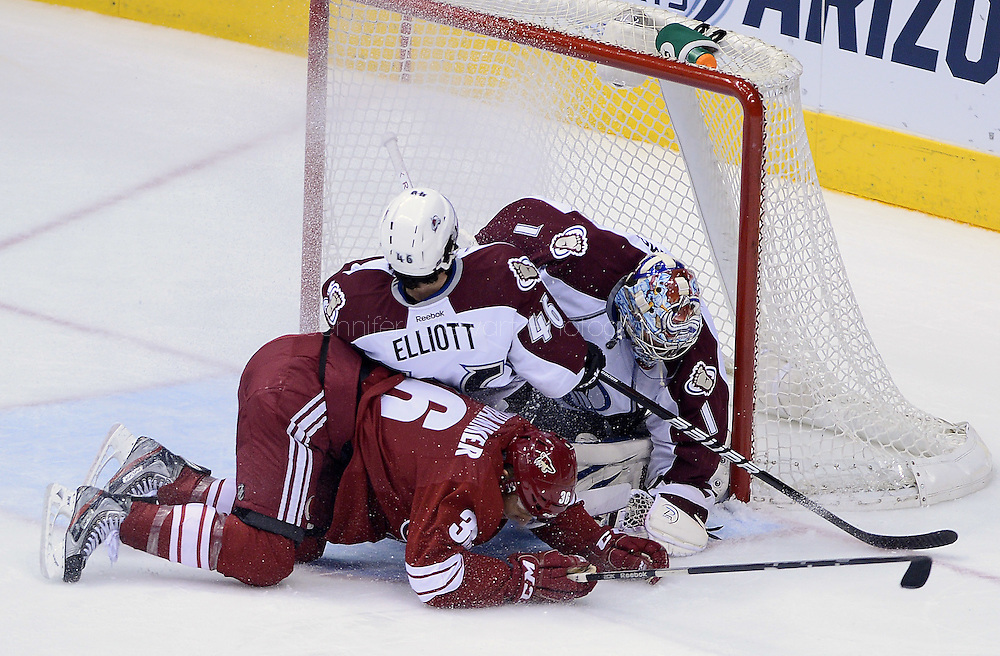 Apr. 6, 2013; Glendale, AZ, USA; Colorado Avalanche goalie Semyon Varlamov (1) blocks the puck in the first period as teammate defenseman Stefan Elliott (46) and the Phoenix Coyotes forward Rob Klinkhammer (36) come sliding into the goal box at Jobing.com Arena. Mandatory Credit: Jennifer Stewart-USA TODAY Sports
