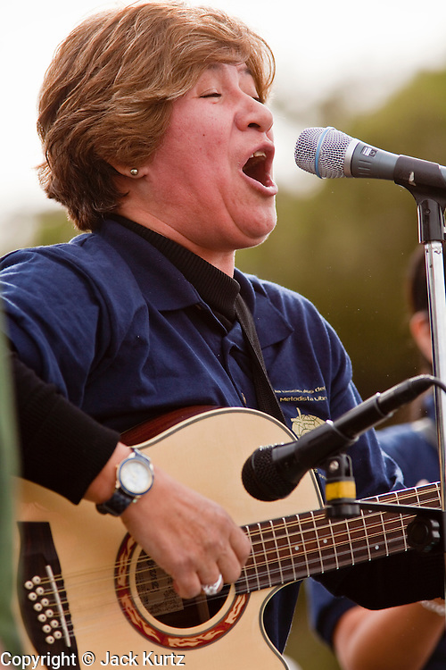 """16 JANUARY 2010 -- PHOENIX, AZ:  Magdalena Schwartz plays guitar during the rally. About 10,000 people marched the 2.5 miles from Falcon Park to the """"Tent City"""" on Durango to protest against Maricopa County Sheriff Joe Arpaio and his immigration enforcement tactics.  PHOTO BY JACK KURTZ"""