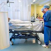 Nederland Rotterdam  25-08-2009 20090825 Foto: David Rozing .Serie over zorgsector, Ikazia Ziekenhuis Rotterdam. ..Foto: David Rozing Serie over zorgsector, Ikazia Ziekenhuis Rotterdam. Een verpleegkundige controleert een patient op de recoveryroom, dit is een zaal waar patienten na een operatie verzorgd worden. Patient is being checked by doctor, in recovery room, where people are looked after, after surgery. ziekenzaal, op zaal liggen Holland, The Netherlands, dutch, Pays Bas, Europe, professionele, professional, steriel, steriele omgeving, werkkleding, kledingvoorschriften, , genezen, genezing, ziekte bestrijding bestrijden, ernstig ziek zijn, ..Foto: David Rozing..Holland, The Netherlands, dutch, Pays Bas, Europe, ronde doen, routine verpleegkundigen, op zaal liggen, behandelplan, treatment,. ,ziektekosten,zorgverlener, zorgverleners,zorgverlening, haarnetje, haarnetjes, overzicht, general view,verpleegster, verpleegsters, verpleger, verplegers, verplegend, status