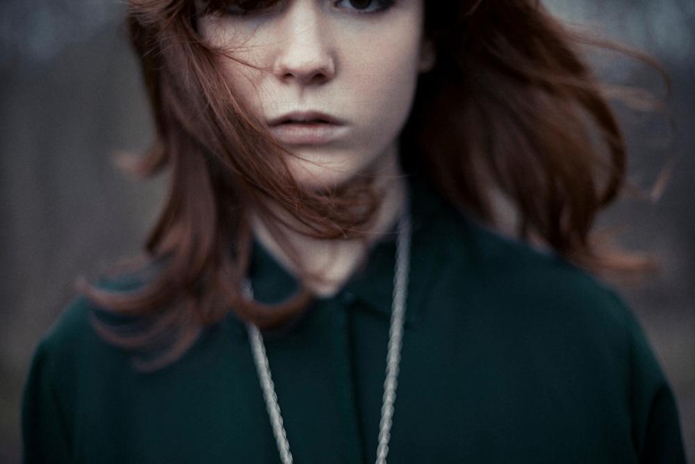 Close up headshot of young woman with sad expression looking at camera
