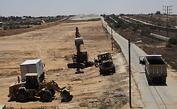 June 28, 2017 - Rafah, Gaza Strip, Palestinian Territory - Palestinian bulldozers clear an area as Hamas begins creating a large buffer zone on the border with Egypt in the southern Gaza strip town of Rafah, on June 28, 2017. The buffer zone is expected to extend for a length of 12 kilometres and at a width of 100 metres along the border, with a road and security cameras running parallel, according to a statement by a security official  (Credit Image: © Ramadan El-Agha/APA Images via ZUMA Wire)