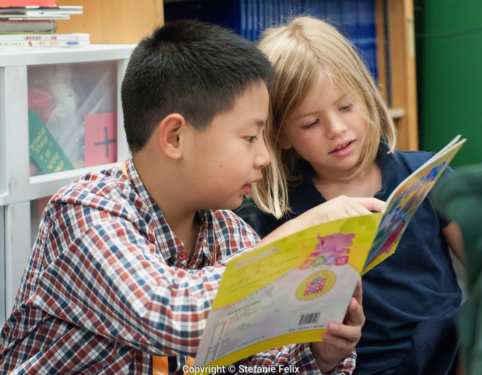 Seattle, Washington: October 2, 2013.  5th grade student from sister school in China, reads to 1st grade Mandarin immersion student at Beacon Hill International School.