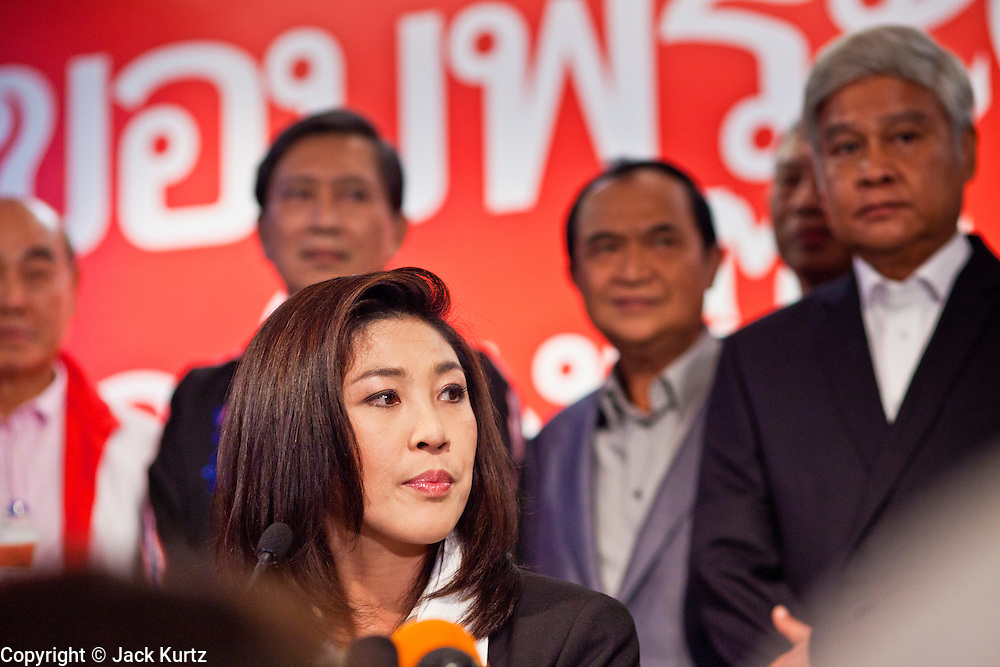 03 JULY 2011 - BANGKOK, THAILAND:  YINGLUCK SHINAWATRA, (seated) the Prime Minister elect of Thailand, is flanked by her advisors while she announces her victory in the Thai elections during a press conference Sunday night. If her election holds she will be the first woman elected Prime Minister of Thailand. Yingluck Shinawatra and the Pheu Thai Party scored a massive landslide win in the Thai election Sunday. Pheu That is estimated to have won more than 300 seats in Thailand 500 seat parliament, so they won an absolute majority and could govern without having to form a coalition with minor parties. Pheu Thai is the latest incarnation of deposed former Prime Minister Thaksin Shinawatra's political party. Yingluck is his youngest sister. Many observers expect legal challenges to the Pheu Thai victory and the election does not completely resolve Thailand's difficult political history of the last five years.     PHOTO BY JACK KURTZ