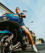 Teenager sitting on his blue motorbike outside a row of houses