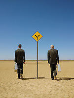 Two businessmen with briefcases walking past road sign in desert back view