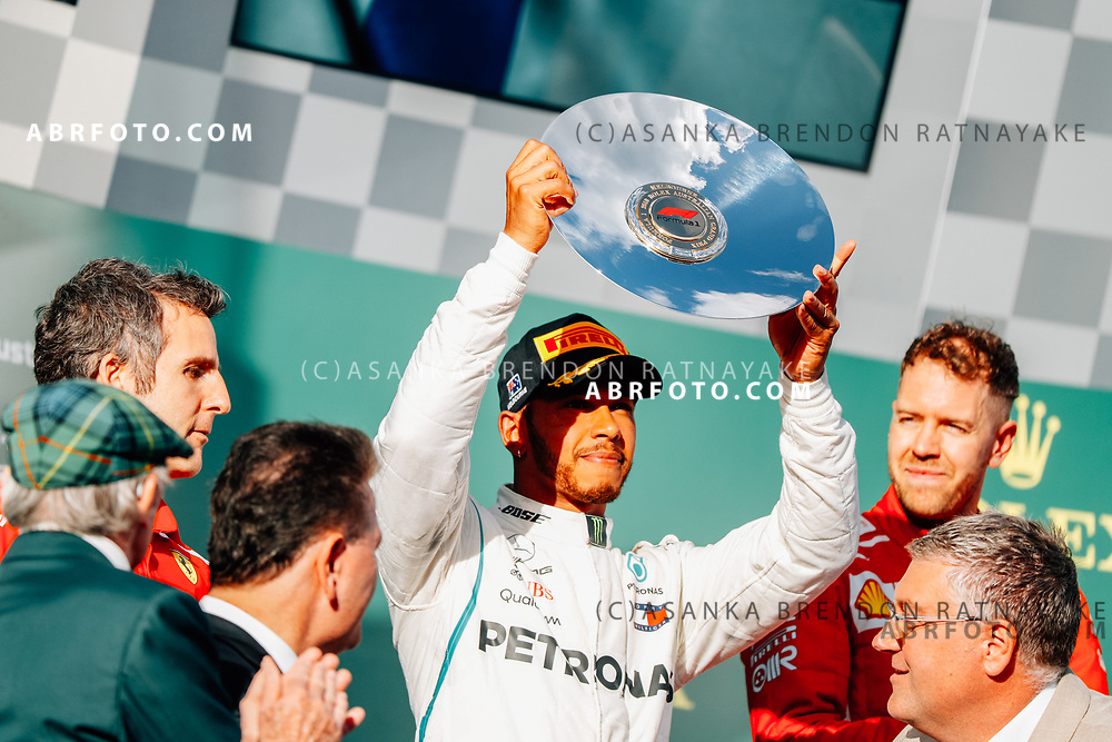 2nd place Mercedes driver Lewis Hamilton of Britain raises his trophy on the podium during the trophy presentation at the end of the 2018 Rolex Formula 1 Australian Grand Prix at Albert Park, Melbourne, Australia, March 24, 2018.  Asanka Brendon Ratnayake