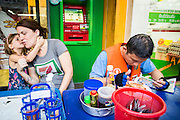 01 APRIL 2013 - BANGKOK, THAILAND:  Arielle Hupe, 4, whispers something to her mother, Amy Hupe, while a motorcycle taxi driver finished his dinner at a street food stall the Hupes stopped at for dinner.   PHOTO BY JACK KURTZ