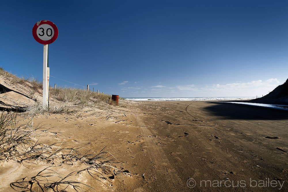 speed sign and tire track enhance this blue sky photo on baylys beach, northland, new zealand