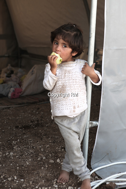 Young Syrian Kurdish refugee eating an apple in her new home - the new refugee camp located in Suruc, Turkey