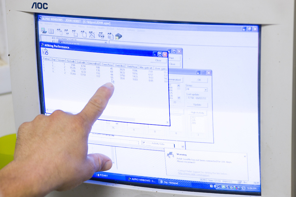 Dairy farmer points with finger at a screen showing milk data