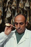 November 1995, Guijuelo, Spain --- A meat inspector tests hams by inserting a horse bone into a joint and smelling it to check the quality of the curing. Guijuelo, Spain. --- Image by © Owen Franken/CORBIS