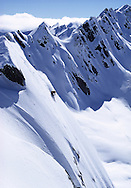 Skier turning in fresh powder snow on steep mountainside, Wanaka, New Zealand