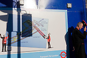An official West End guide in front of a London Crossrail construction site hoarding.