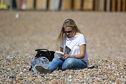 © Licensed to London News Pictures. 19/09/2014. Brighton, UK. Friday September 19th 2014 lunchtime on Brighton Beach. People relaxing on the beach during lunch in Brighton. The weather is expected to reach temperatures around 4C in Brighton and the South Coast. Photo credit : Hugo Michiels/LNP