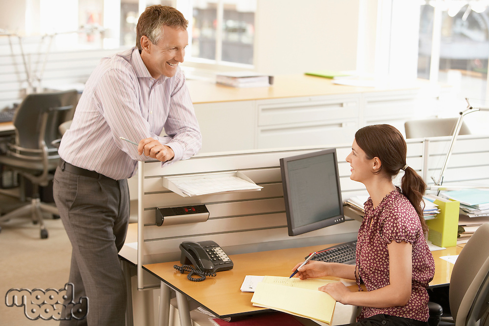 Male office worker talking to female office worker at cubicle