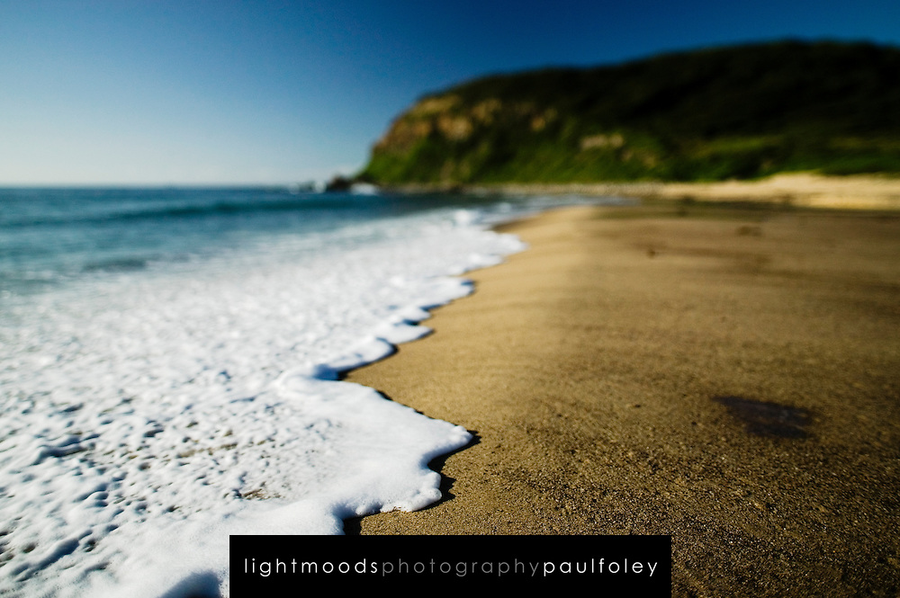 Selective focus close up views of foam and sand. East Coast Australia.
